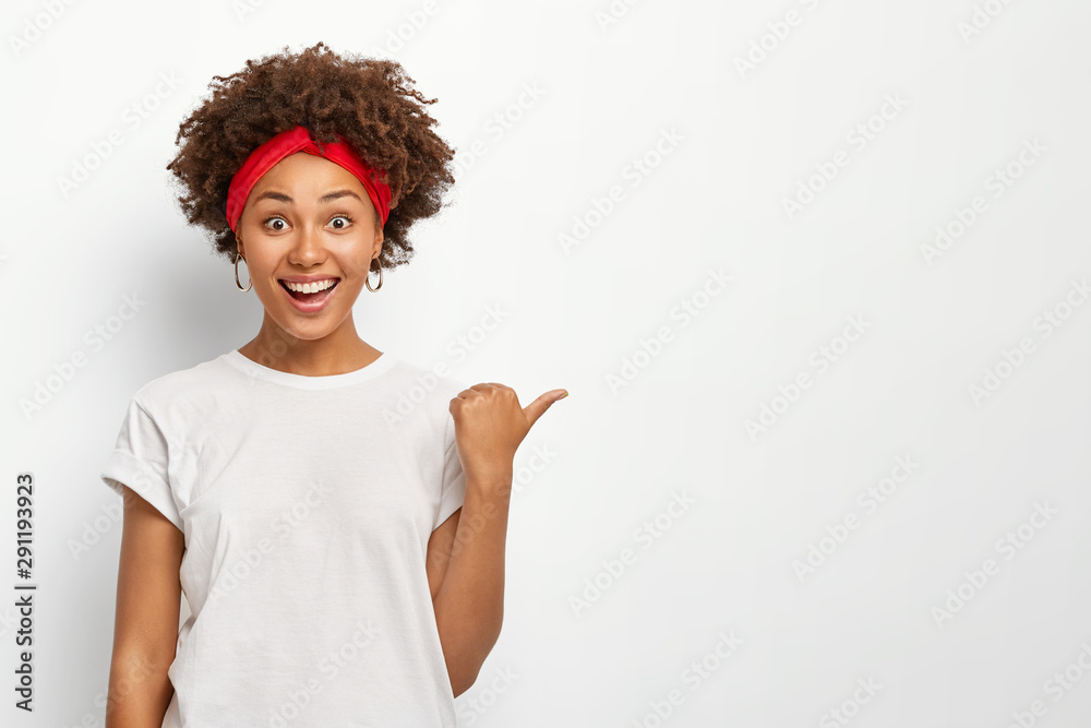 Fototapeta Joyful dark skinned young African American woman points away right with thumb, dressed in casual wear, demonstrates copy space for your advertising content, smiles happily, recommends something