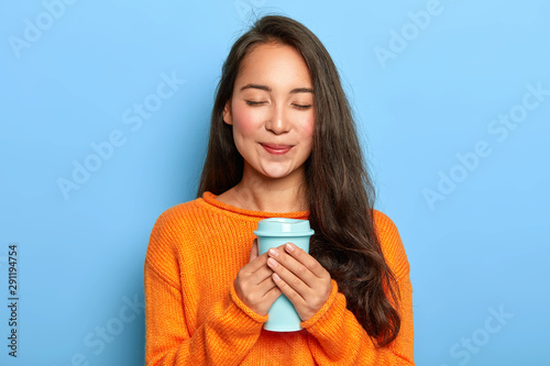 Fototapeta Pleased restful girl with Asian appearance, keeps eyes closed, smiles gently, enjoys drinking aromatic espresso from takeout cup, wears orange jumper, isolated over blue background