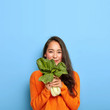 canvas print picture - Satisfied Korean woman with pleased face expression, buys healthy dieting food, holds raw green vegetable, going to make tasty vegetarian lunch, wears casual orange jumper, poses over blue wall