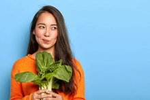Photo Of Attractive Young Woman Holds Fresh Green Vegetable, Eats Healthy Food At Home, Uses Food Product For Making Vegetarian Salad, Wears Orange Jumper, Poses Indoor. Home Growing Concept.