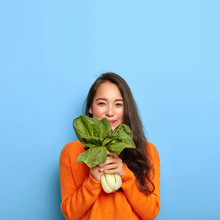 Satisfied Korean Woman With Pleased Face Expression, Buys Healthy Dieting Food, Holds Raw Green Vegetable, Going To Make Tasty Vegetarian Lunch, Wears Casual Orange Jumper, Poses Over Blue Wall