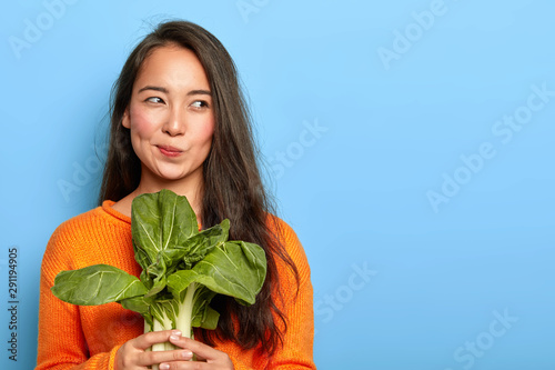 Fototapeta Photo of attractive young woman holds fresh green vegetable, eats healthy food at home, uses food product for making vegetarian salad, wears orange jumper, poses indoor. Home growing concept. obraz