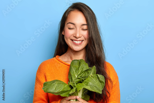 Fotografia  Pleased Asian woman with dark long hair holds green bok choy vegetable, going to