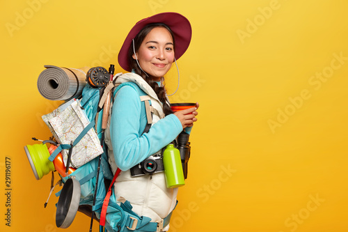 Canvastavla Pleased young Asian female traveler stops on her way to have coffee break, wears