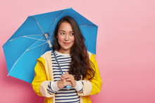 Photo Of Pretty Thoughtful Woman With Dark Straight Hair, Holds Blue Umbrella, Walks During Cool Day, Protects Herself From Rain, Wears Yellow Raincoat, Enjoys September, Poses Over Pink Background