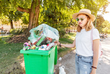 The Annoyed Girl Throws The Garbage Into The Already Filled Garbage Container. The Concept Of Environmental Pollution And Inaction Of The Authorities