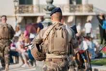 An Unidentified Man In Military Uniform And With A Military Weapon Patrolling The Streets Of The City During A Public Event.
