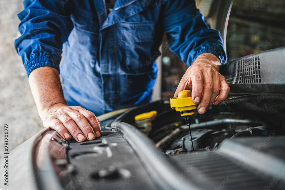 Fototapeta Car service worker checking oil and repairing motor at auto service cente