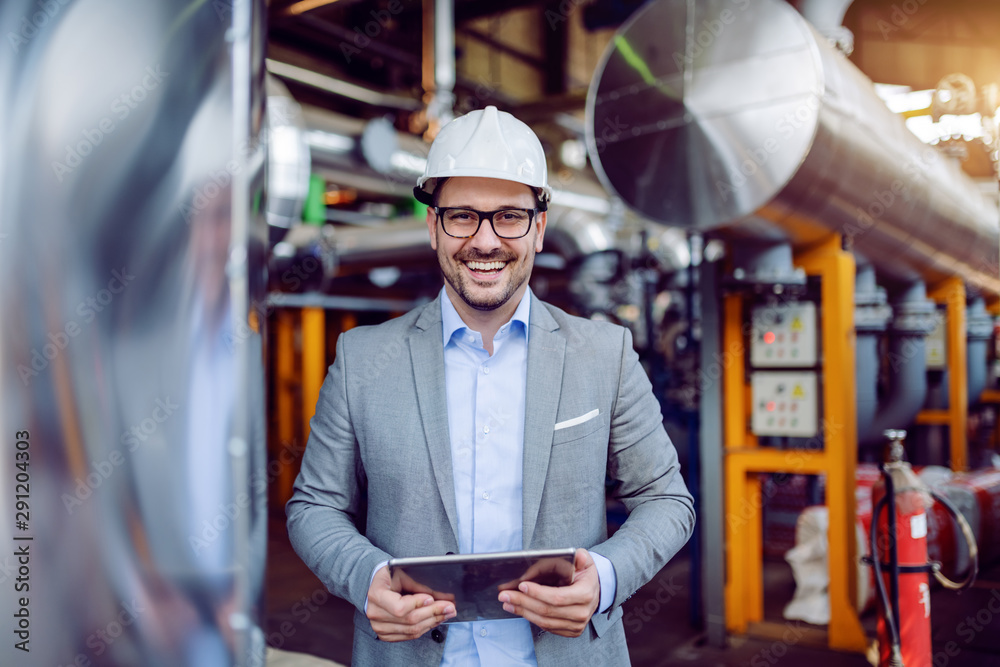 Fototapety, obrazy: Smiling attractive caucasian supervisor in gray suit and with white helmet on head holding tablet while standing in power plant.