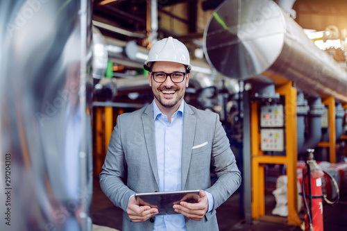 Fotografie, Obraz  Smiling attractive caucasian supervisor in gray suit and with white helmet on head holding tablet while standing in power plant