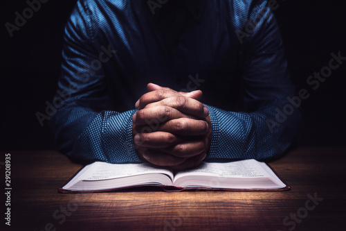 Man praying on a wooden desk Fototapeta