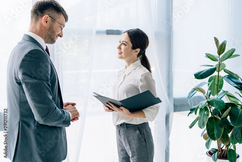 side view of journalist talking with businessman in formal wear