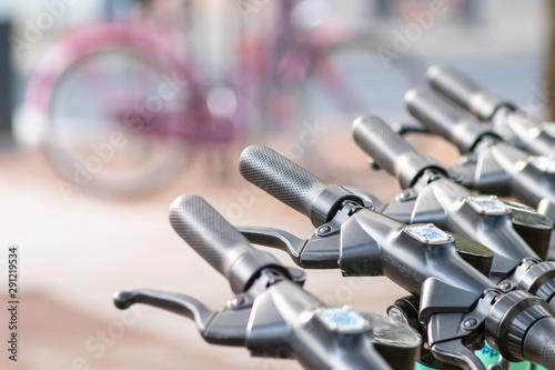 Lenker von E-Scootern im Vordergund mit Fahrrad im unscharfen Hintergrund als Ge Wallpaper Mural