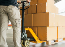 Warehouse Worker Working With Hand Pallet Truck And Goods Pallet Shipment Unloading At Distribution Warehouse, Business Industry Delivery Transportation,