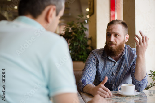 Photographie  two men discussing difficult issues with emotions during coffee break in cafe ta