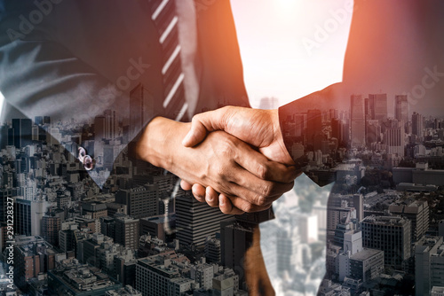 Double exposure image of business people handshake on city office building in background showing partnership success of business deal Wallpaper Mural