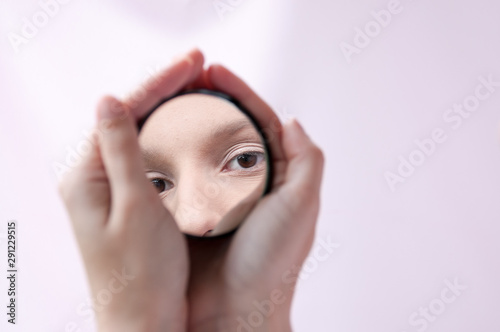 Hands holding a mirror with a reflection of the girl's eyes