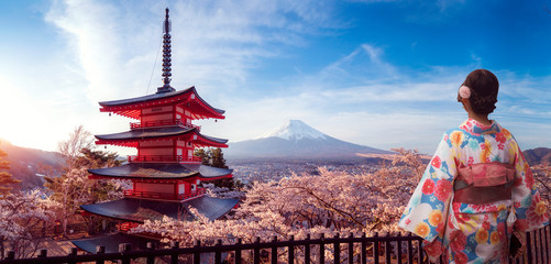 Japanese girl in kimono traitional dress walk in Sakura park with Fuji mountain background