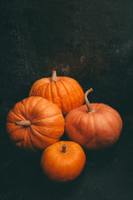 Photo Of Four Orange Pumpkins On Black Background, Halloween Celebration, Space For Inscription.