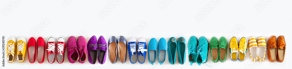 Fototapeta A lot of colored youth women's shoes without heels. Sneakers, slippers, ballet shoes. White background.