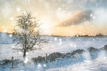Beautiful snow covered Winter landscape at sunrise in Peak District in England in heavy snow storm