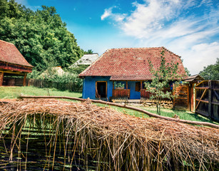 Fototapeta na wymiar Captivating summer view of traditional romanian peasant houses. Amazing rural scene of Transylvania, Romania, Europe. Beauty of countryside concept background.
