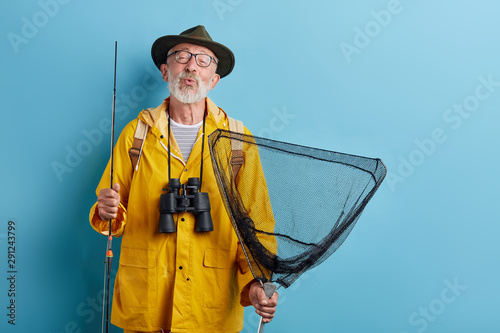 Photo funny old man with binocular, rod and net in yellow raincaot and grren hat blowing kiss, whistling close up photo