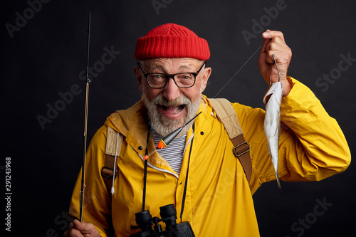 Obraz na plátně Happy old bearded fisherman with binocular wearing red casual hat and yellow anorak holding in hand fish which he catched on sea last night