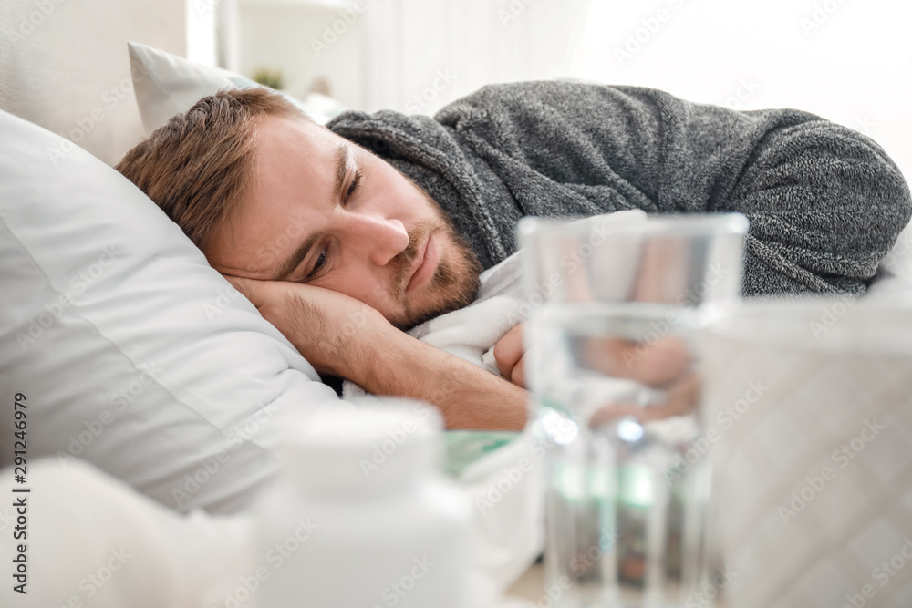 Fototapeta Man ill with flu lying in bed