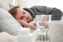 Man Ill With Flu Lying In Bed
