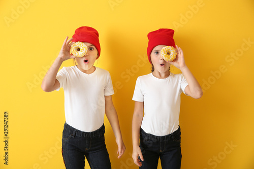 Photo Portrait of surprised twin girls with tasty donuts on color background