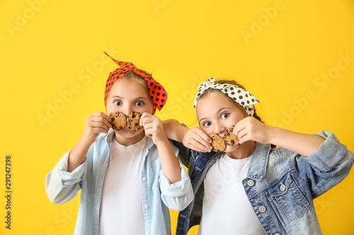 Obraz Portrait of funny twin girls with cookies on color background - fototapety do salonu
