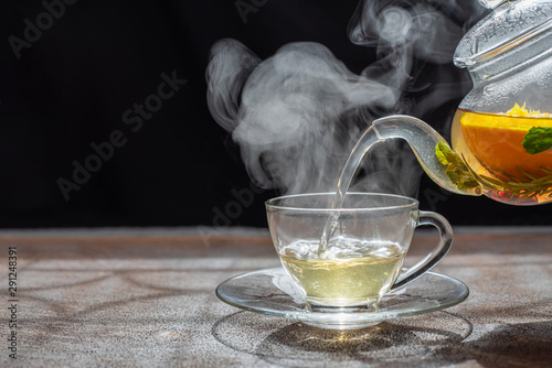 Tuinposter Thee Process brewing tea,dark mood.The steam from hot tea is poured from the kettle into a kettle with tea leaves redcurrant mandarin orange lemon,rosemary, mint.,hot food and healthy meal concept