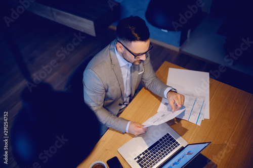 Poster Ecole de Danse Top view of serious Caucasian handsome man in suit and with eyeglasses sitting in dining room in morning and holding bills. On table is laptop. Online bills payment concept.