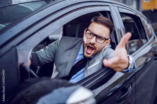 A sharp dressed man finding himself caught in a rush hour and slowly succumbing to the road rage Fototapet