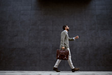Full Length Of Stylish Caucasian Designer In Gray Sweater Holding Leather Bag While Passing By Gray Wall.
