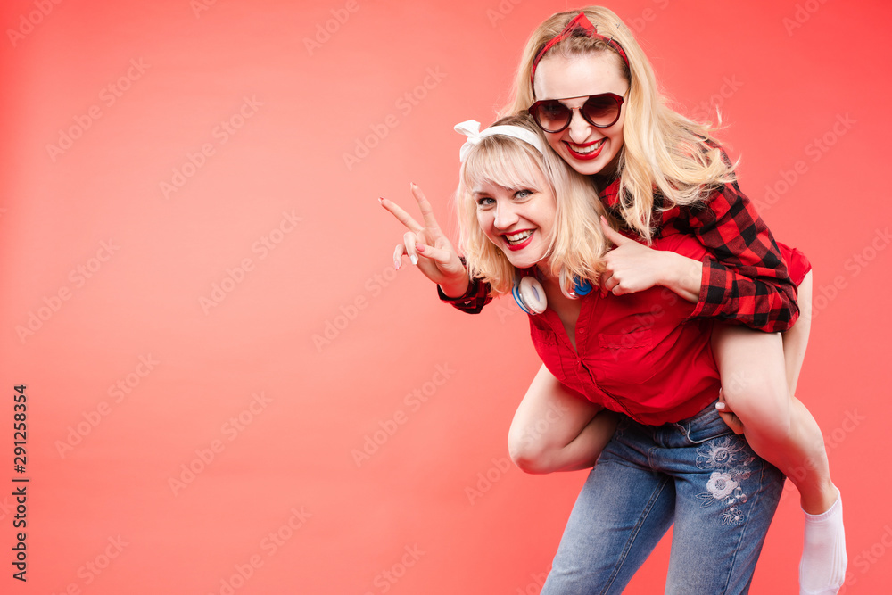 Fototapety, obrazy: Stock studio portrait of two cheerful and positive trendy girlfriends or sisters having fun. Girl in sunglasses making bunny ears to her friend with her hand while sitting on her back. Isolate on red.