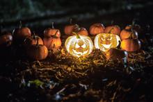 Halloween Jack-o-lantern On Autumn Leaves. Scary Halloween Pumpkin Looking Through The Smoke. Glowing,