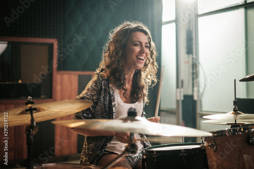 Woman playing drums during music band rehearsal - 291259722