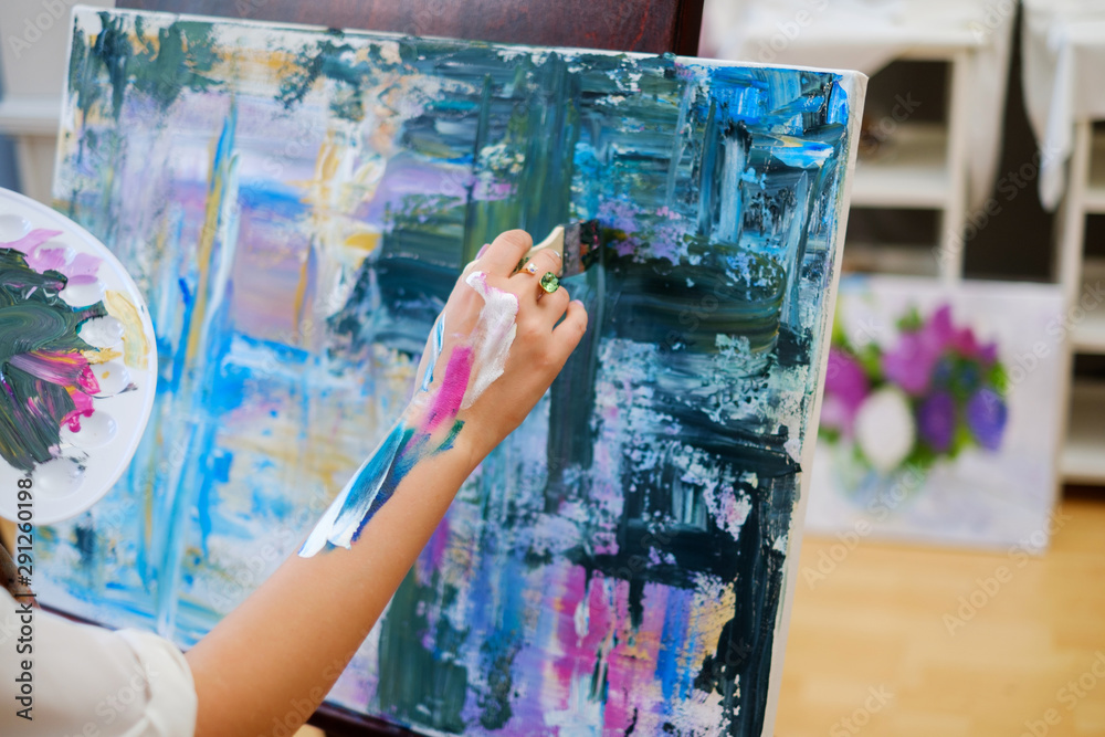 Fototapeta Creative painter paints a colorful picture in her studio