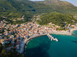Parga Greece drone aerial view. Crystal water natural landscape and beautiful architectural buildings near the port of Parga Epirus, Greece, Europe.