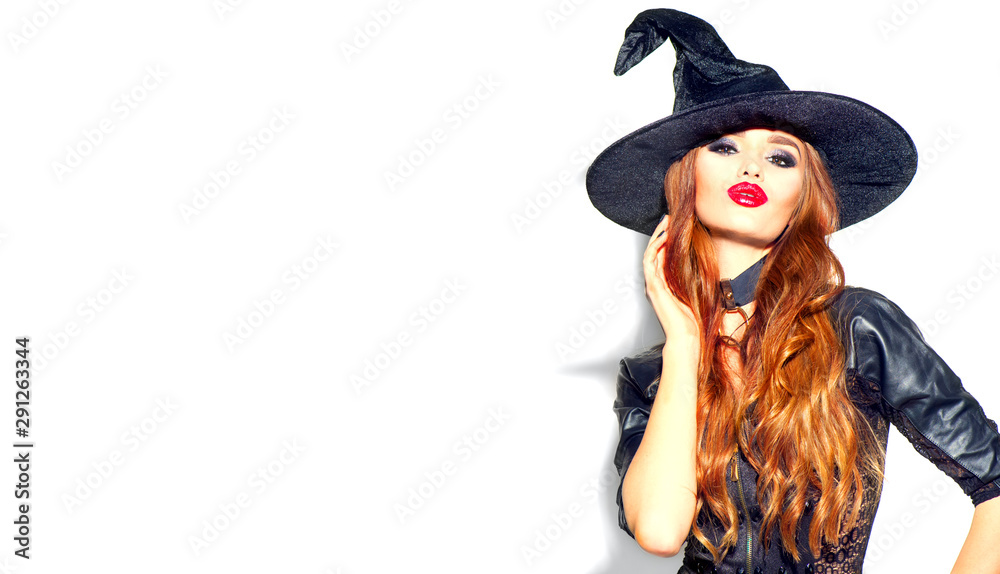 Fototapeta Halloween Sexy Girl wearing witch costume with a hat. Party, Celebrating. Beauty Woman with long red hair and holiday bright make-up isolated on white background. Leather dress