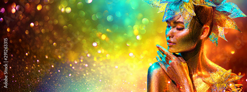 Golden Fashion model woman with bright golden sparkles on skin posing, fantas...