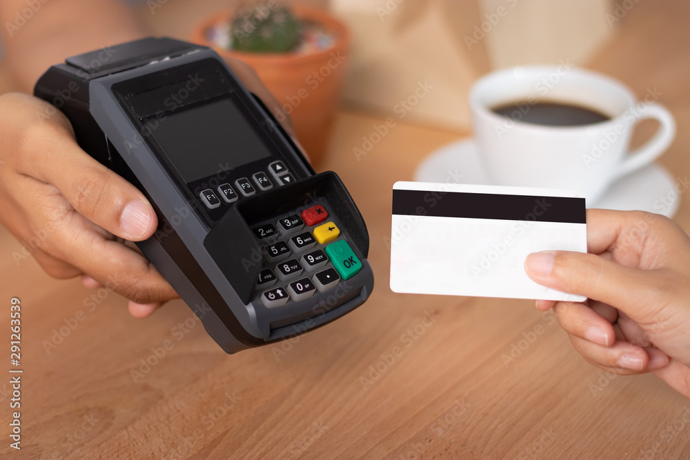 Fototapeta hand of customer using credit cart for payment at point of sale terminal in shop during shopping time, cashless technology and credit card payment concept