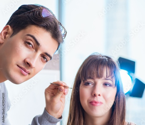 Man doing make-up for cute woman in beauty salon #291264331