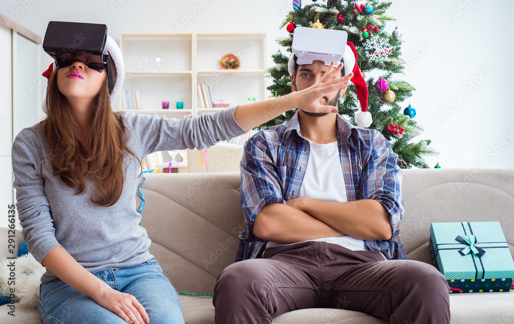 Fototapeta Happy family using virtual reality VR glasses during christmas