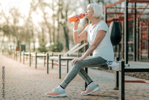 Fotomural  Beautiful aged sports-oriented woman drinking water from the bottle
