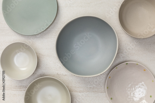 Group of empty blank ceramic round bowls and plates on white stone blackground, Top view of traditional handcrafted kitchenware concept