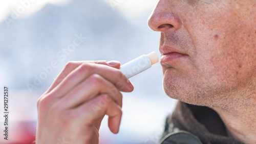 Photo Handsome, Mature, bearded man using natural lips balm on light gray background