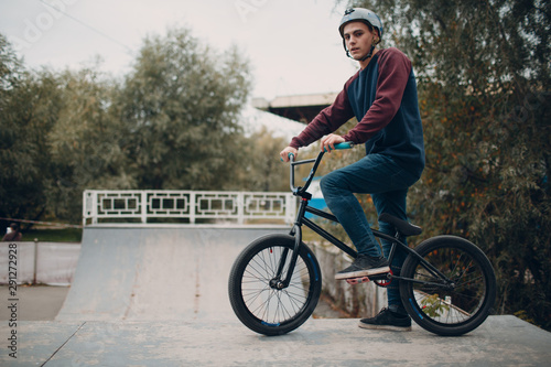 Professional young male sportsman cyclist with bmx bike at skatepark